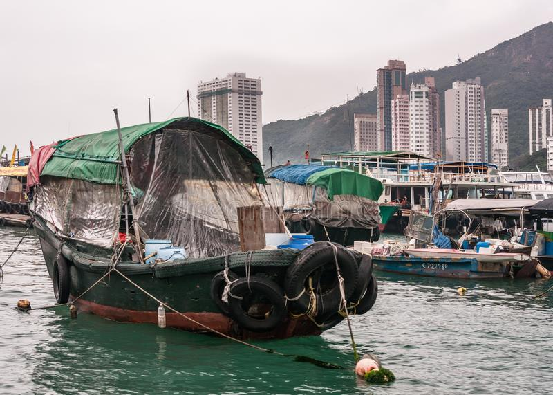 Closeup of one houseboat in harbor of Hong Kong, China. Hong Kong, China - May 12, 2010: Closeup of Green and black wooden old houseboat in harbor. Sloops around stock images