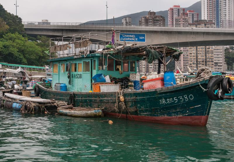Closeup of one houseboat in harbor of Hong Kong, China. Hong Kong, China - May 12, 2010: Closeup of Green and brown wooden old houseboat in harbor. Sloops around royalty free stock photo