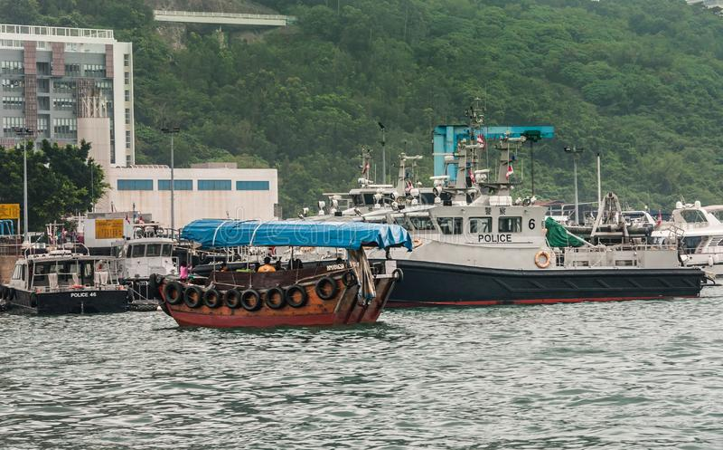 Police boats in harbor of Hong Kong, China. Hong Kong, China - May 12, 2010: Group of gray and black police boats moored in harbor. Sampan moving in front on royalty free stock photography