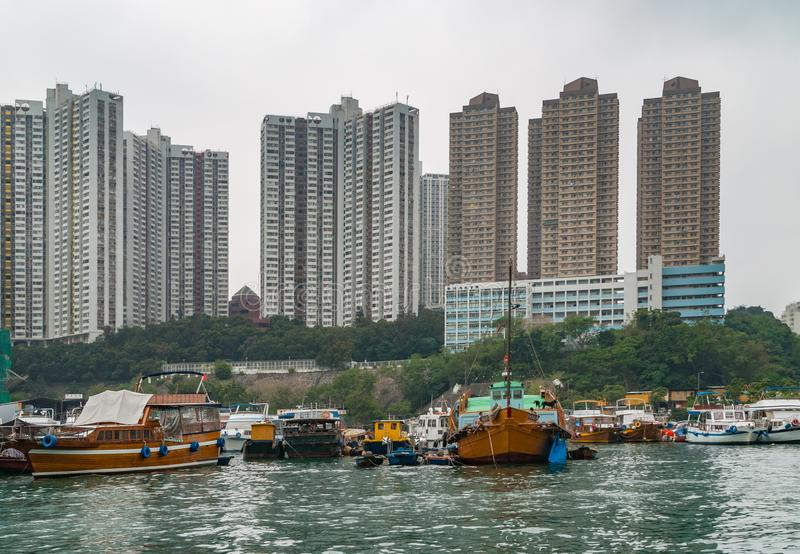 Highrise buildings in harbor of Hong Kong, China. Hong Kong, China - May 12, 2010: Highrise buildings behind Yacht and houseboats harbor under foggy silver sky royalty free stock photography