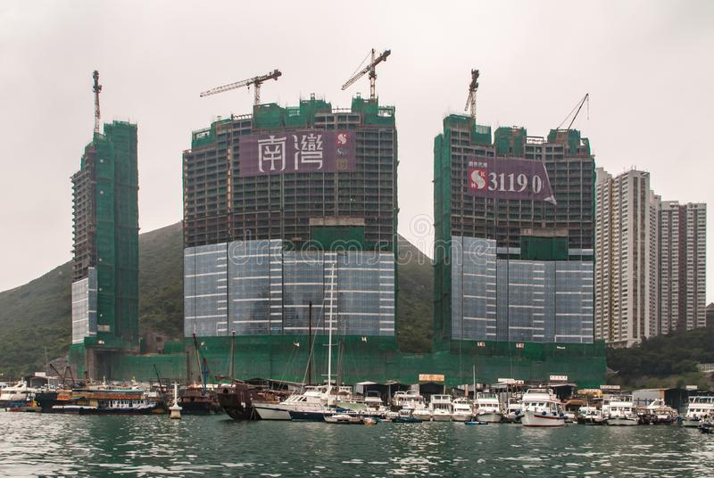 Highrise under construction in harbor of Hong Kong, China. Hong Kong, China - May 12, 2010: Highrise complex of three towers under construction behind Yacht and stock photo