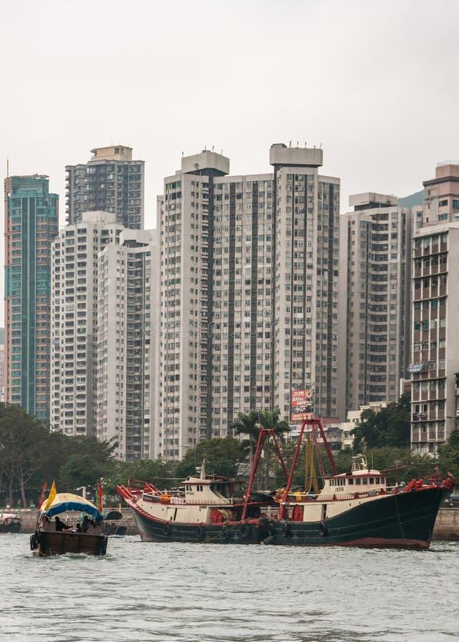 Highrise building behind fishing vessels in harbor of Hong Kong, China. Hong Kong, China - May 12, 2010: Very tall gray and green highrise buildings behind black royalty free stock photography