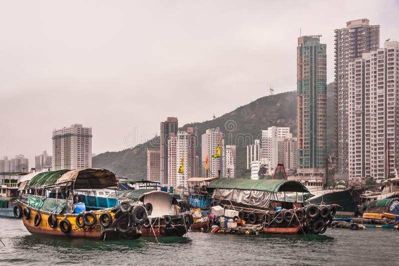 Highrise building behind ferries in harbor of Hong Kong, China. Hong Kong, China - May 12, 2010: Very tall gray and green highrise buildings behind green, yellow royalty free stock images