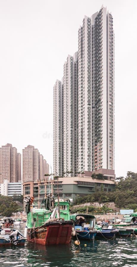 Highrise building behind houseboats in harbor of Hong Kong, China. Hong Kong, China - May 12, 2010: Very tall highrise buildings behind Blue and white old stock photo