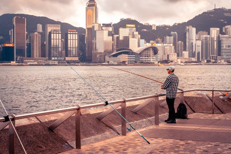Hong Kong, China - Oude mens die in de haven vissen stock foto's