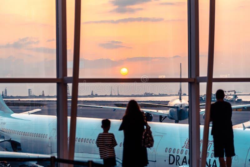 Hong Kong, China - pasajeros que miran la puesta del sol en el terminal de la salida foto de archivo