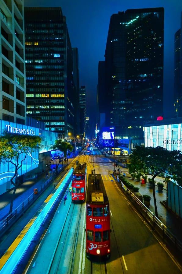 HONG KONG, CHINE - 29 AVRIL 2014 : La vie de nuit du ` s de Hong Kong Deux trams rouges passent le long de la rue avec les boutiq images libres de droits