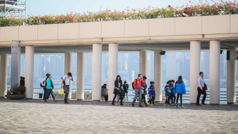 Hong Kong, Cina - 1° gennaio 2016: I residenti ed i turisti urbani passano sotto il ponte sulla costa di Hong Kong E immagini stock libere da diritti