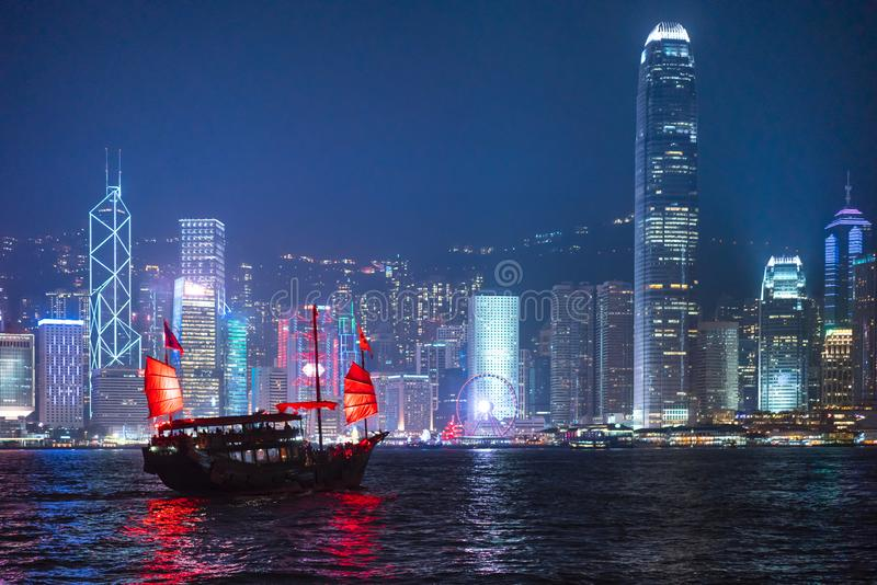 Hong Kong City skyline with tourist sailboat at night. View from across Victoria Harbor Hong Kong stock photos