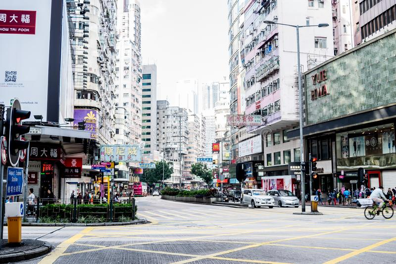 Hong Kong - December 11, 2016: View of Hong Kong road traffic  and people against with the commercial buildings in Kowloon side of royalty free stock image