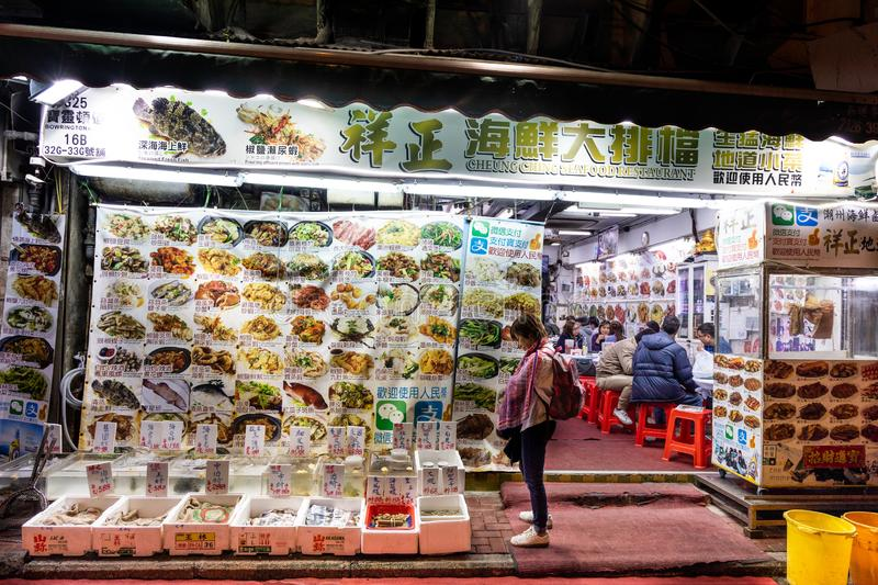 HONG KONG, February 9, 2019: Tourists browsing various small restaurant that serves fresh live seafood.  royalty free stock photos