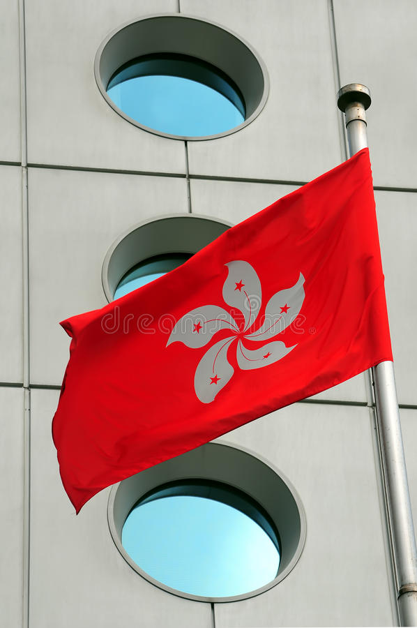 Hong kong flag. Blowing in the wind against building windows royalty free stock photos