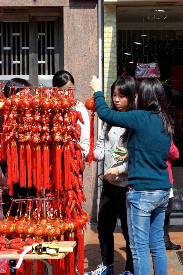 Hong Kong: Folk som shoppar för röda kinesiska garneringar för nytt år royaltyfri foto