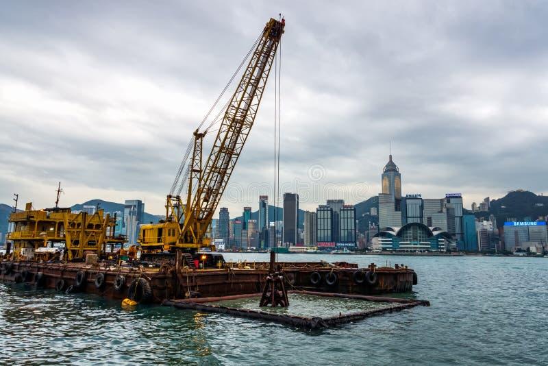 In Hong Kong-Hafen ausbaggern, Schlamm, Unkräuter und Abfall heraus schaufelnd lizenzfreie stockfotos