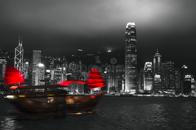 Hong Kong harbor at night with blurred silhouette of sailboat stock images