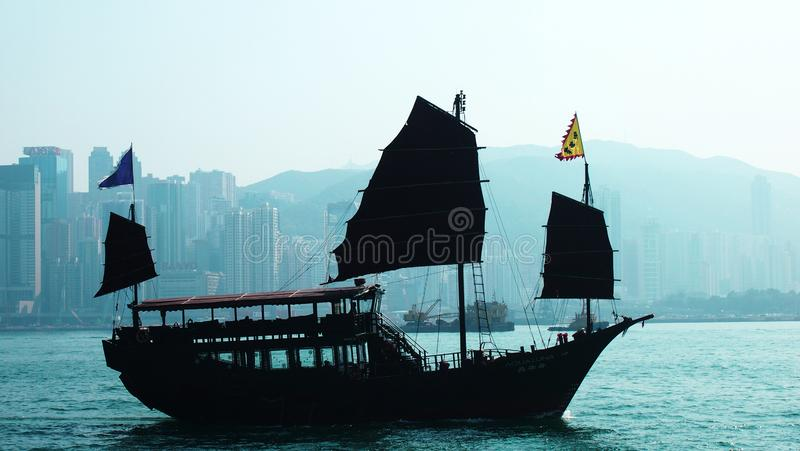 Hong Kong Harbor wooden ship. Silhouette sea view with building faraway royalty free stock images