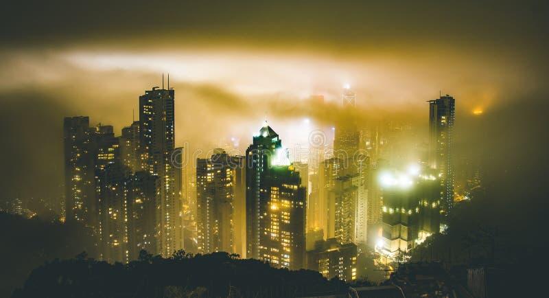 Hong Kong horisont från Victoria Peak på en dimmig dimmig natt - det Wandelrust loppbegreppet runt om South East Asia huvudstäder arkivbild