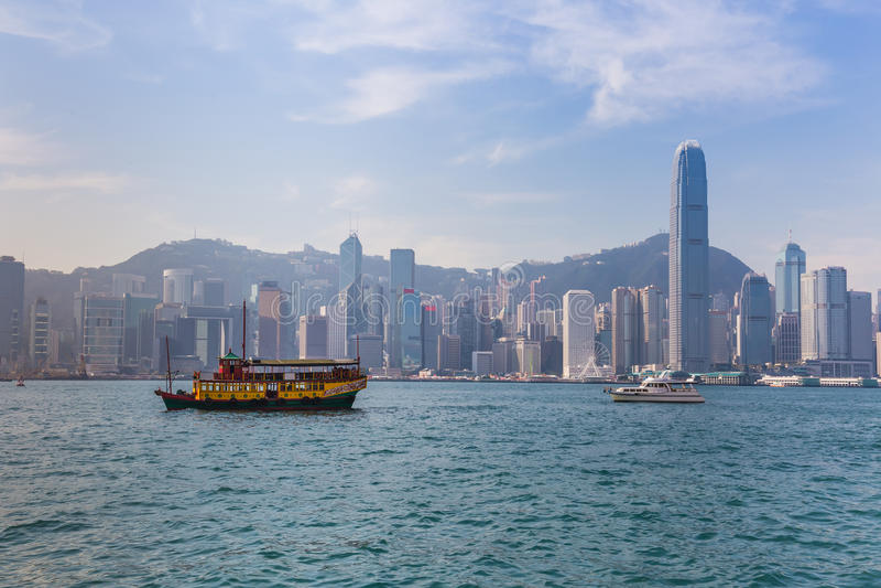 Hong Kong horisont med fartyg i den Victoria hamnen royaltyfri foto