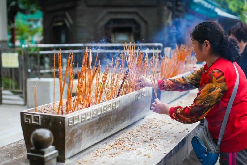 HONG KONG IM APRIL 2018 - chinesische Dame betet in Wong Tai Sin Temple Frauenlichter verärgern im Tempel lizenzfreie stockfotos