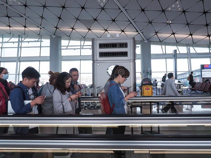 Hong Kong International Airport/Hongkok - 11 avril 2018 : Le passager jouent un téléphone de moblie silding sur l'escalator à l'i photo stock