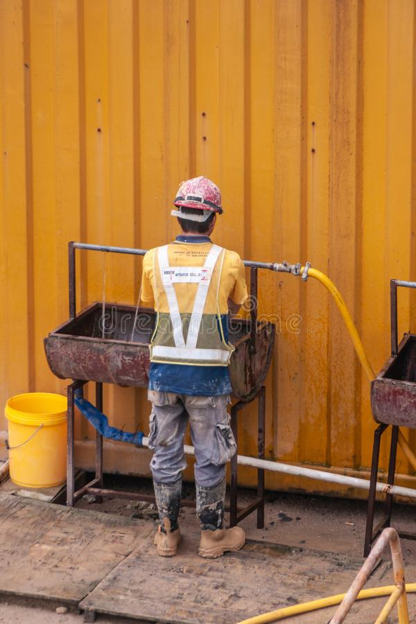 Construction worker washes hands on Hong Kong Island, China stock photos
