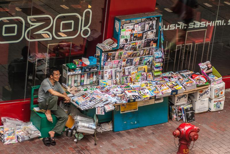 Magazine and newspaper stand along street, Hong Kong Island, China. Hong Kong Island, China - May 14, 2010: Newspaper and Magazine and magazine stand shop with stock image