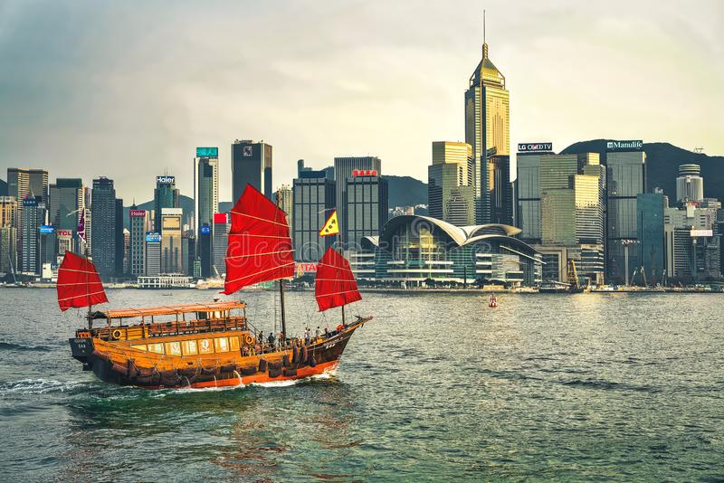 Junk boat in Victoria Harbor in Hong Kong at sunset. View from Kowloon on HK Island. Hong Kong, Hong Kong -March 6, 2016: Junk boat in Victoria Harbor in Hong stock images