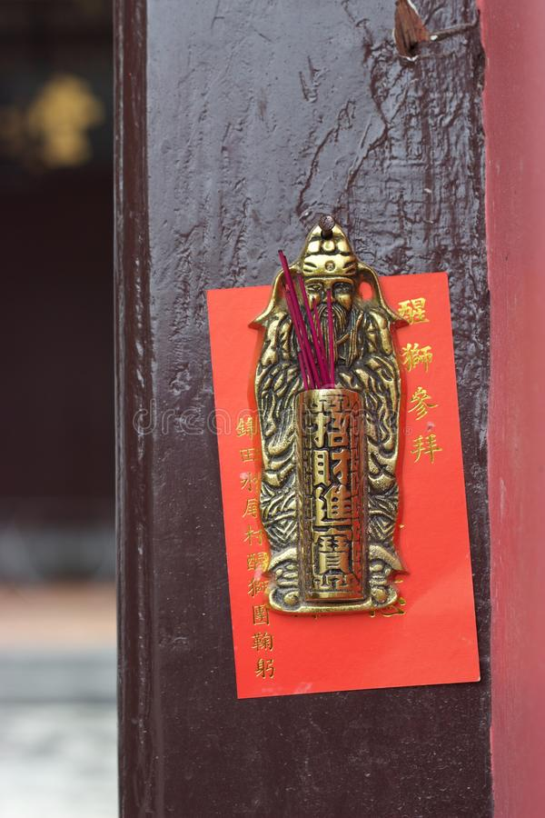 Hong Kong New Territories temple: incense in bronze holder. At a temple in the city`s New Territories, incense sticks rest in a bronze holder hanging on a wooden royalty free stock image