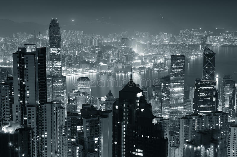 Hong Kong at night in black and white. Hong Kong city skyline at night with Victoria Harbor and skyscrapers illuminated by lights over water viewed from mountain royalty free stock image
