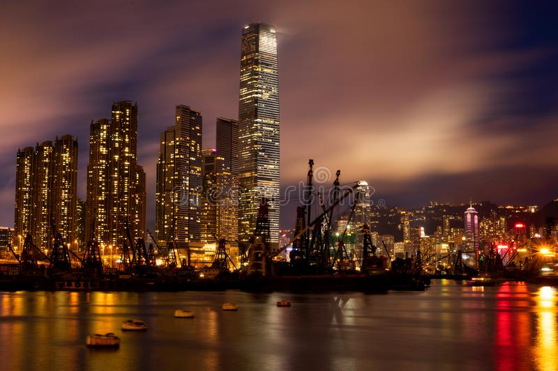 Hong Kong night view. View of the International Commerce Centre through the harbor. Night scene with boats. Crane in harbor for containers. Illuminating stock images