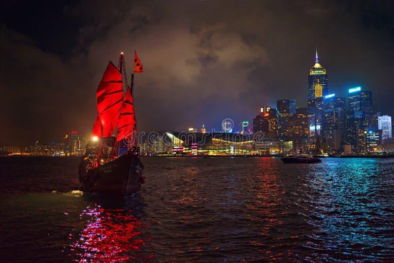 Hong Kong - November 19, 2015: Sailboat and Hong Kong harbor at night. Hong Kong - November 19, 2015: Traditional boat with red sail and harbor at night royalty free stock photo