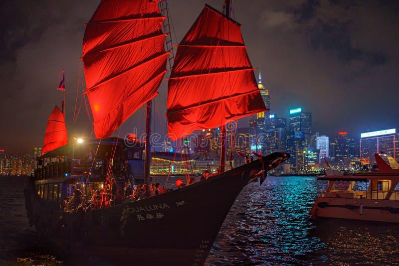 Hong Kong - November 19, 2015: Sailboat and Hong Kong harbor at night. Hong Kong - November 19, 2015: Traditional boat with red sail and harbor at night stock photos