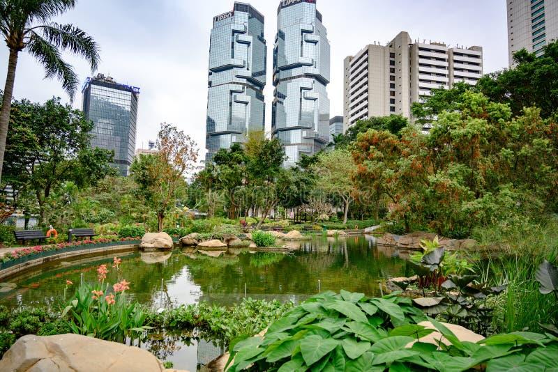 Hong Kong Park med skyskrapor från Lippo Center i ryggen arkivbilder