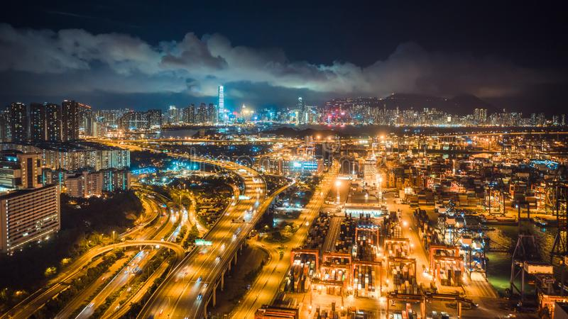 Hong Kong port, highway traffic, and the Symphony of Lights show on buildings in city at night. Asia tourism, logistic business royalty free stock image