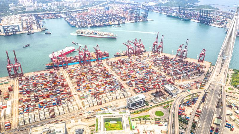 Hong Kong port industrial district with cargo container ship, cranes, car traffic on road and Stonecutters bridge. Logistic industry or freight transportation royalty free stock photography