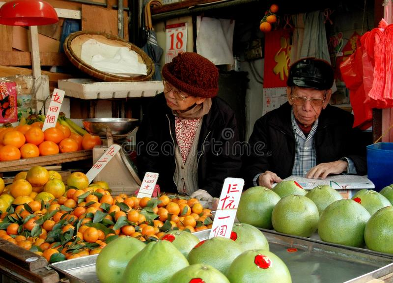 Hong Kong: Reclamation Street Market. An elderly couple sitting inside their small booth at the Reclamation Street market selling various fruits including stock photography