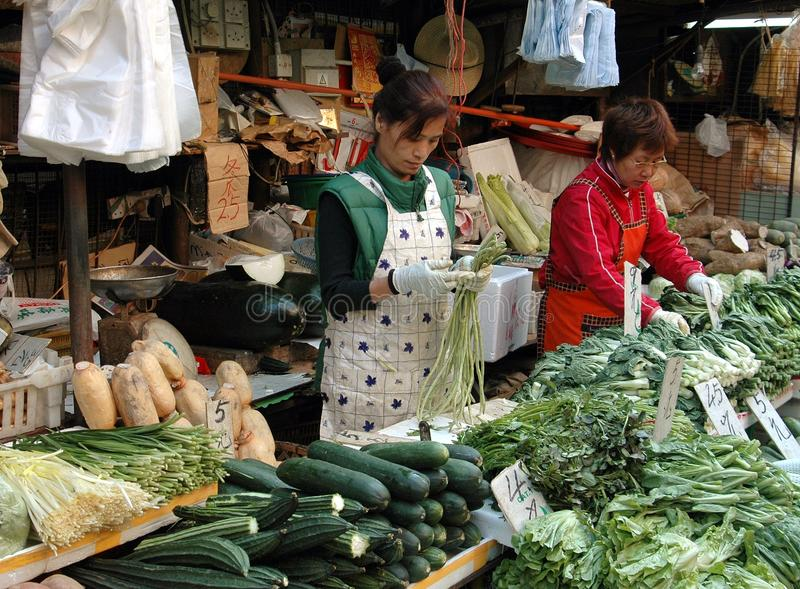 Hong Kong: Reclamation Street Market. Two women selling vegetables from their both at the expansive Reclamation Street outdoor food market in Kowloon, Hong Kong royalty free stock photo
