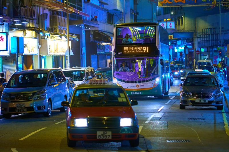 HONG KONG - September 5, 2017: Asian metropolis traffic scene wi. Th double decker bus and red taxi cab during evening rush hours. Vibrant colors of night city royalty free stock photography