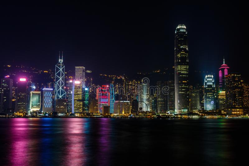 Hong Kong Skyline at night from across the harbor. The skyline of Hong Kong Island at night, as seen from across the harbor at Tsim Sha Tsui ferry pier stock photo