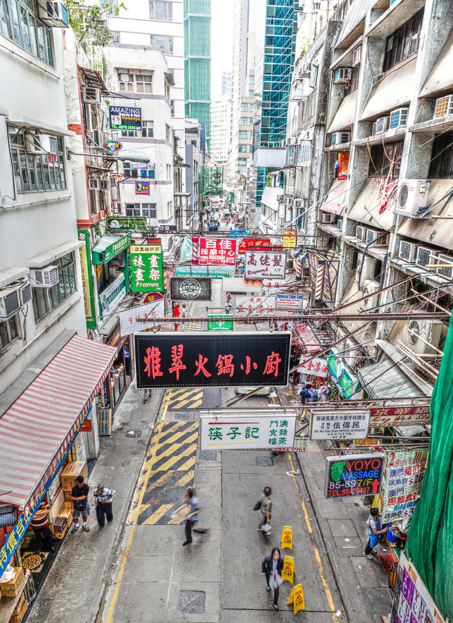 Hong Kong Street Scene in Landmark Central District. Hong Kong, China - March 30, 2015: Multiple street billboard ads hang on rafters along a busy street in the royalty free stock image