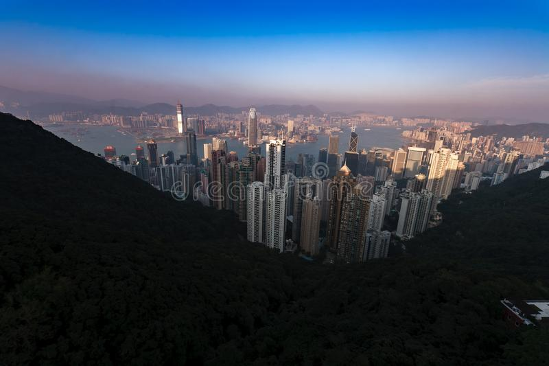 Skyline view of Hong Kong Harbor at sunset from Victoria Peak across the harbor. Hong Kong at sunset from Victoria Peak across the harbor royalty free stock photography