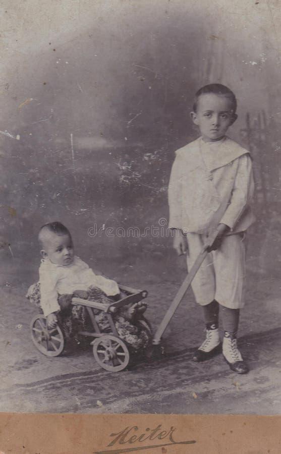 HONGARIJE SZà  SZRà ‰ GEN REGHIN CIRCA 1890 - Weinig jongen die zijn jongere broer met vervoer tracting - Kabinetsfoto - royalty-vrije stock afbeelding