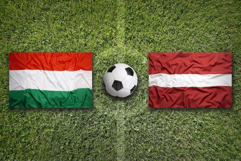 Hongarije versus Nederland De vlaggen van Letland op voetbalgebied stock foto