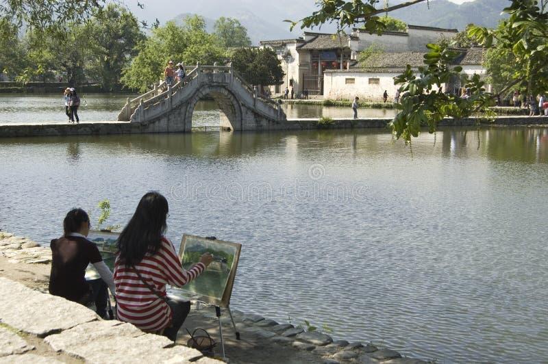 Hongcun bridge and artists. Artists painting the famous bridge at Hongcun, Anhui, China stock photo