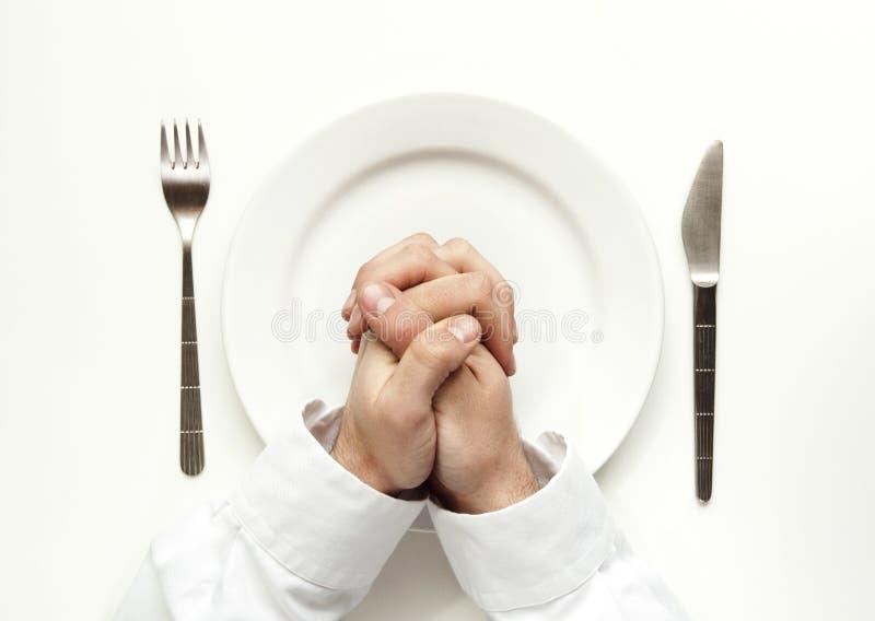 Honger. Het bidden voor voedsel op wit wordt geïsoleerd dat. stock afbeelding