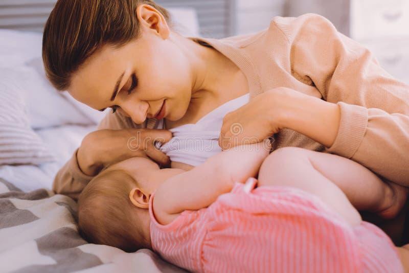 Hongerig babymeisje die naast haar de borst gevende moeder liggen stock afbeeldingen