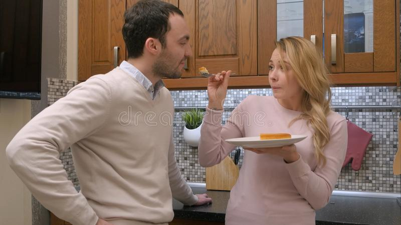 Hongerig paar die heerlijke cake, vrouwen voedende man, in de keuken thuis eten royalty-vrije stock foto's
