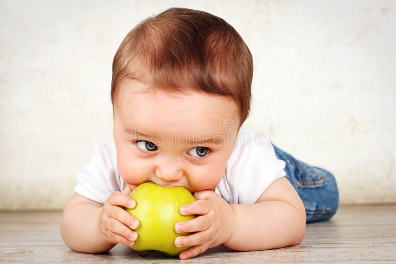 Hongerig weinig babyjongen die appel eten royalty-vrije stock afbeeldingen