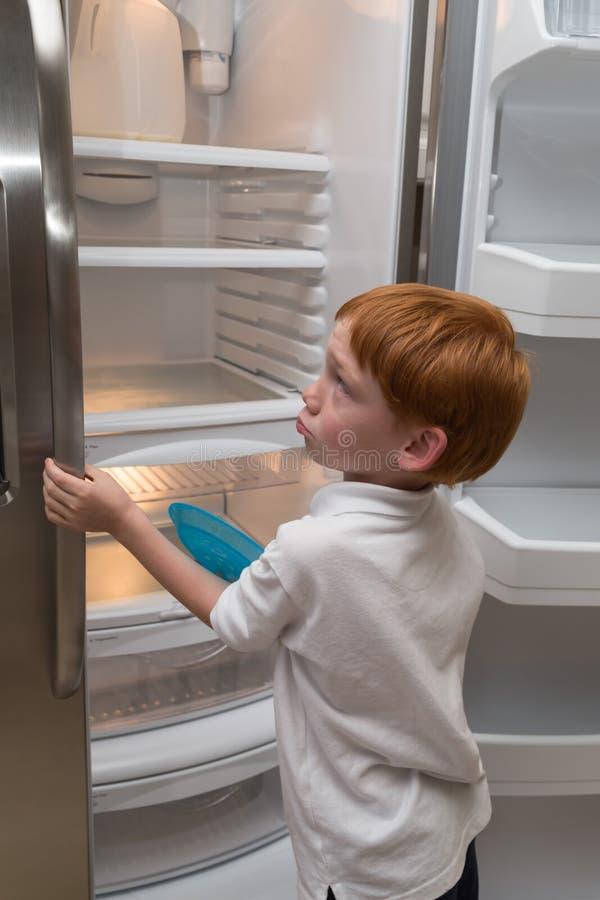 Hongerig weinig jongen die lege koelkast onderzoeken stock afbeelding
