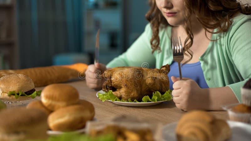 Hongerig zwaarlijvig wijfje die met vettige braadstukkip, spanning het eten voorbereidingen treffen te dineren stock foto's